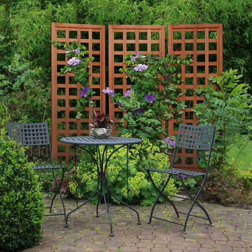 Wooden lattice trellis with climbing clematis used as patio privacy