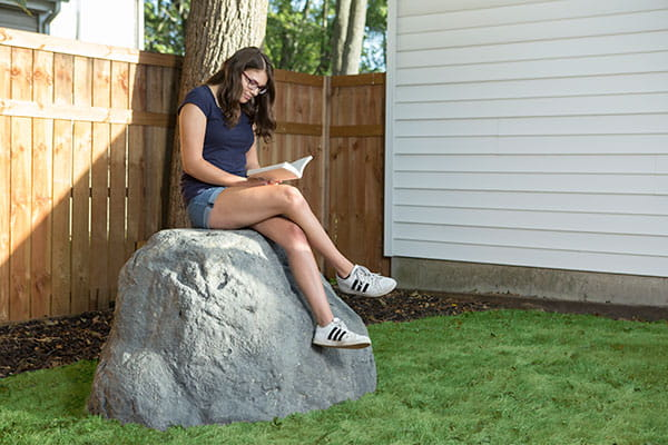 Giant hollow artificial landscape rock with teen reading book