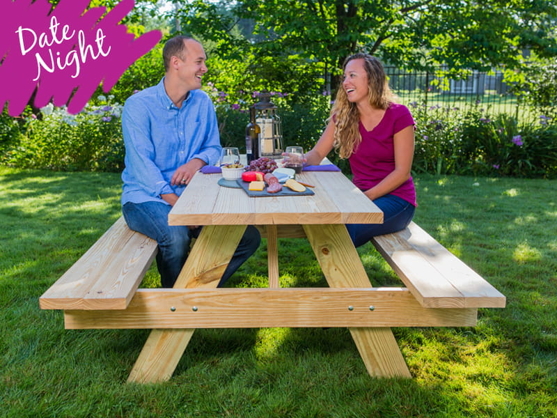 Outdoor Essentials wood picnic table with wine and cheese date night