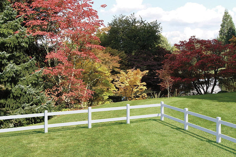 White 2 rail vinyl ranch rail fence marking backyard property lines