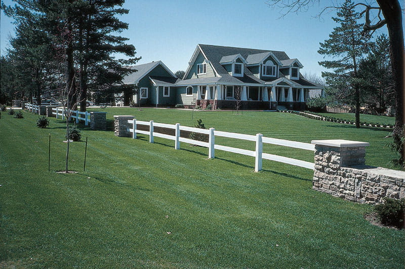 Mixed material fence vinyl ranch rail and stone posts and stone wall
