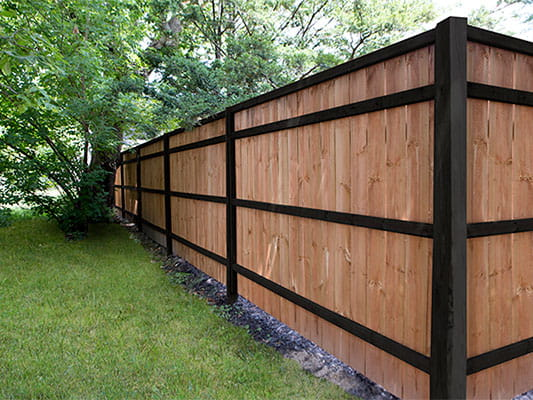 Two tone fence with Cedar Tone Pickets and Black Posts and Backer Rails